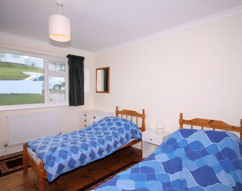 A simple twin bedroom at Zapadiah, a holiday cottage within walking distance of the beach, at Polzeath, Cornwall