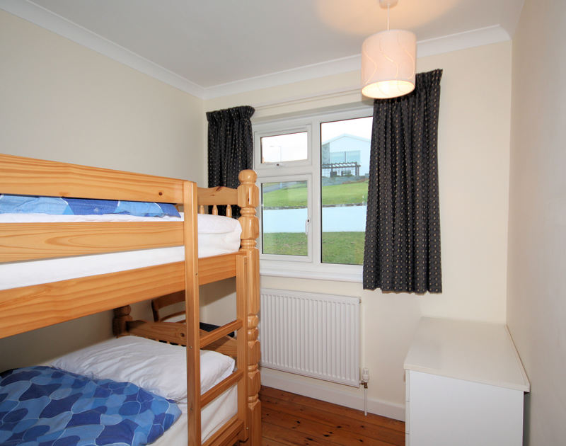 A cosy bunk room with 2 bunk beds at Zapadiah, a self-catering holiday let at Polzeath, Cornwall