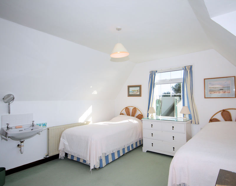 A bright and spacious twin bedroom with a hand basin at Thalassa, a self catering holiday home in cliff top position above Greenaway Beach, Daymer, Cornwall.