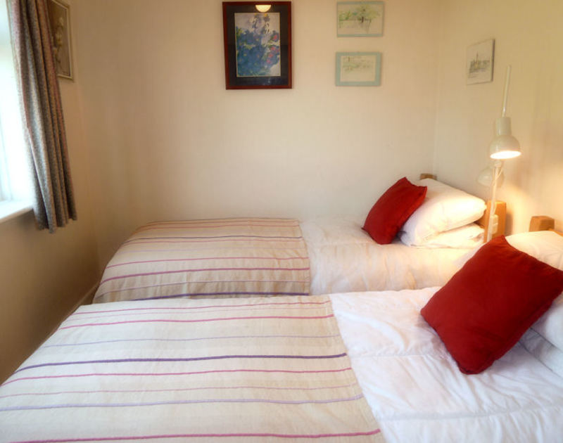 Cosy twin bedroom with window overlooking the rear garden in self catering holiday bungalow Caelum, in Port Isaac, North Cornwall.