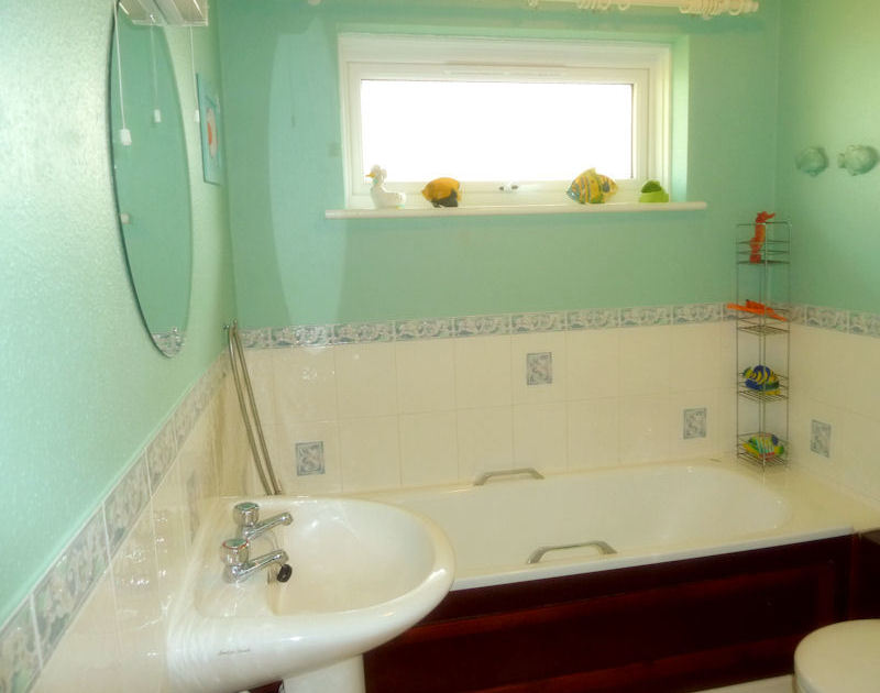 Holiday rental Caelum in Port Isaac, North Cornwall offers brightly painted bathroom with wash hand basin, WC and bath with window over.