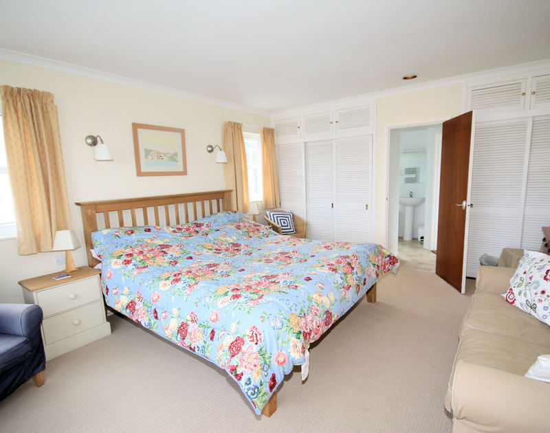 The spacious master bedroom with en-suite at Tristram Steps, a self catering holiday rental in Polzeath, North Cornwall.