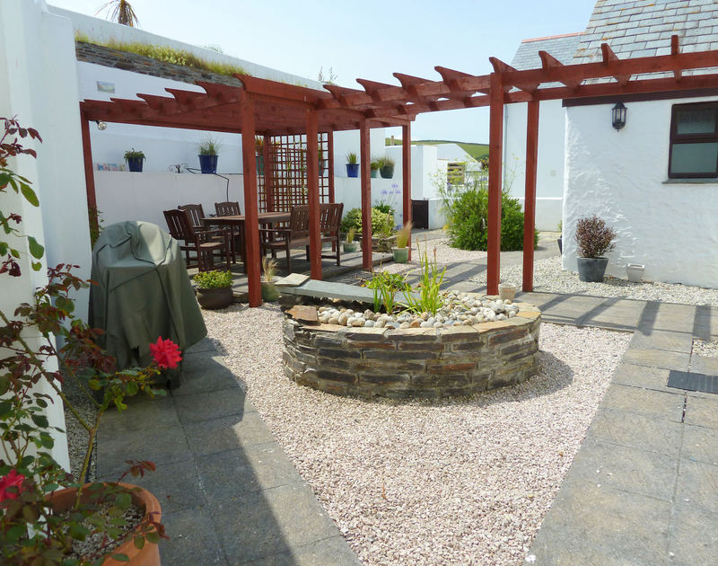 Very attractive terraced rear garden of 1 Cliffside, with raised dining area and steps to upper garden in Port Isaac, North Conrwall