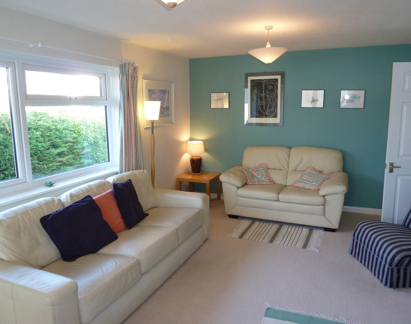 The bright sitting room with large window and comfortable white leather sofas in Caelum, a self catering holiday rental in Port Isaac, Cornwall.