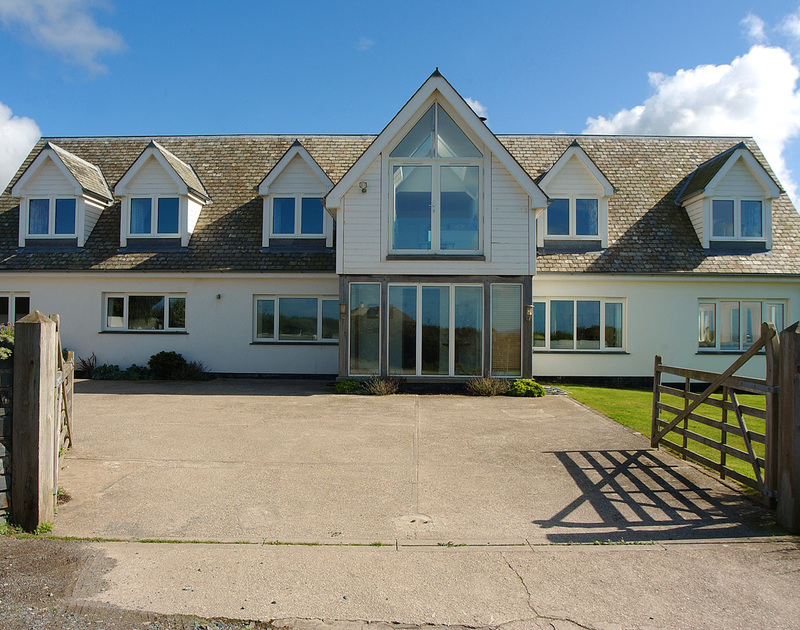 The exterior of Greenaway Heights, a holiday house near Daymer Bay, Cornwall, with large driveway and 5-bar gates.