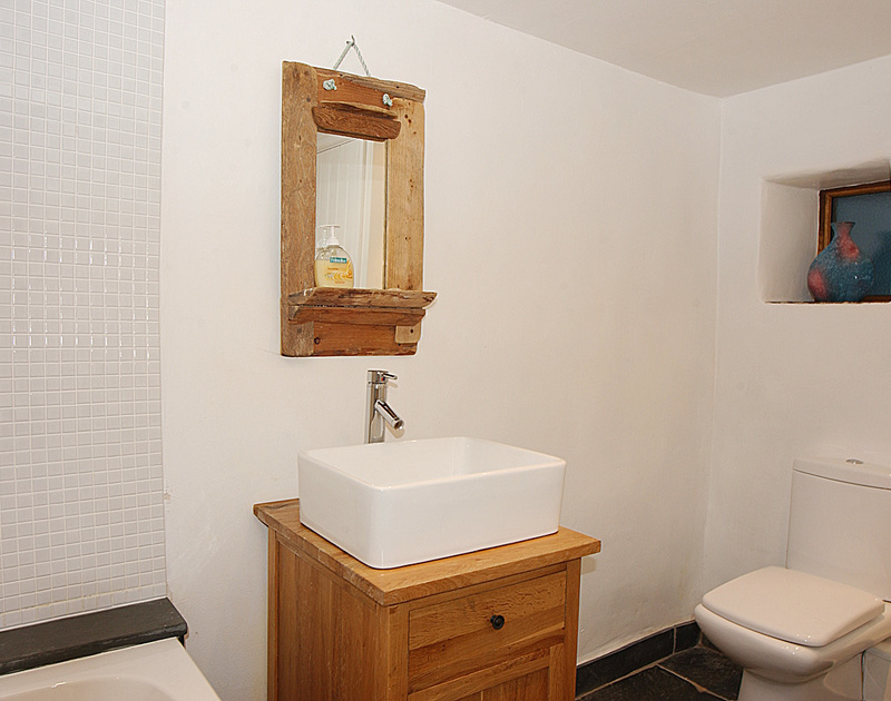 The attractive bathroom of Little Tides, a holiday rental in Rock, Cornwall, with its driftwood mirror.