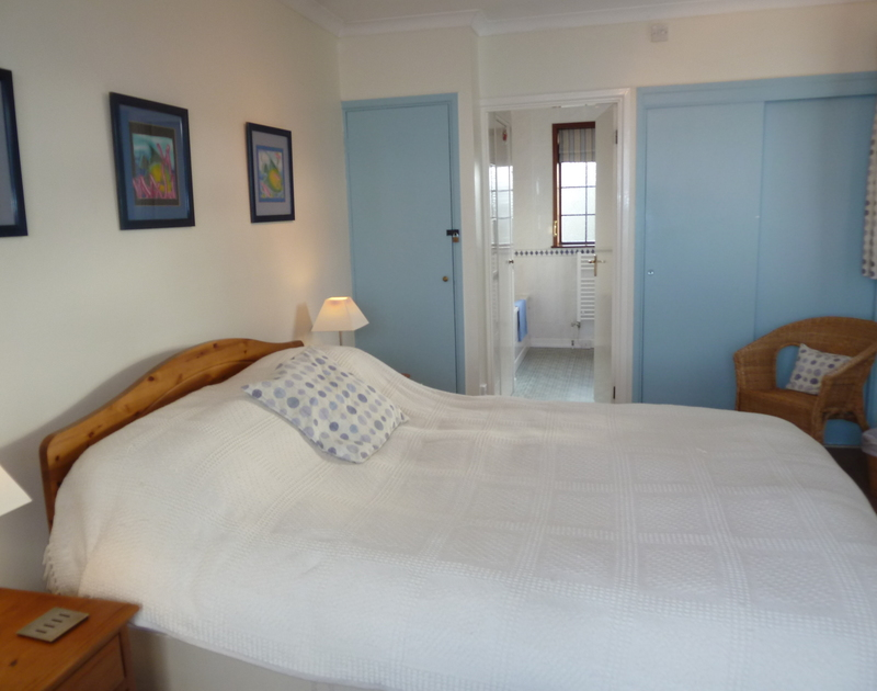 King size bed in the master bedroom with en suite bath/shower room in self catering holiday cottage Shilling Stones in Port Isaac, North Cornwall.