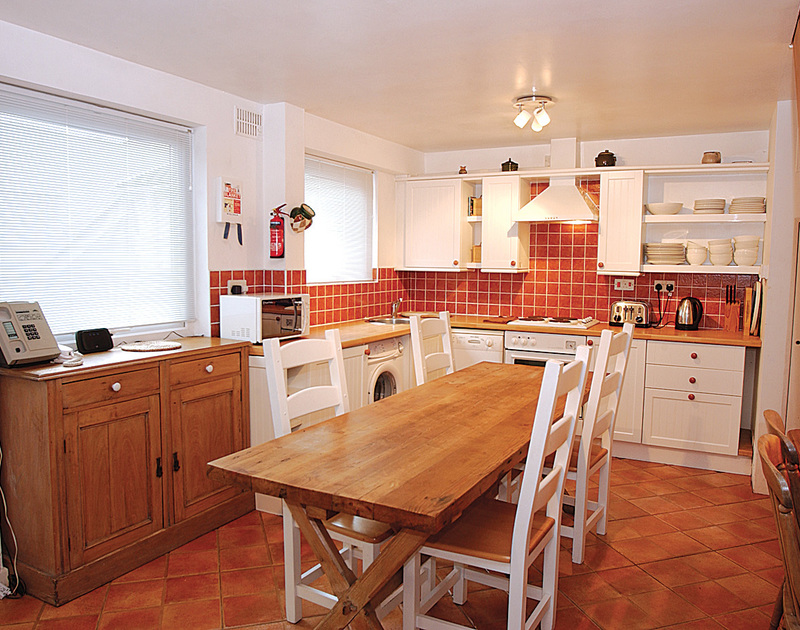 Cheerful kitchen with wooden dining table at 3 Overcliff, a self-catering holiday house in Port Isaac, Cornwall,