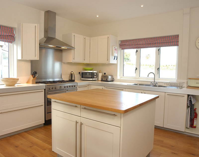 The contemporary kitchen and useful kitchen island in Medrose 2, a self catering holiday house to rent in Rock, North Cornwall.