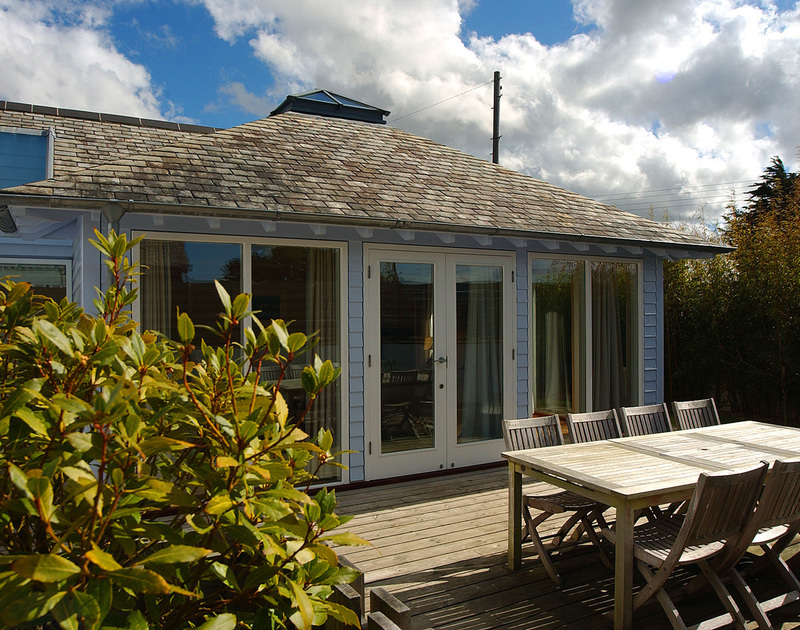 A sunny decked terrace with garden furniture at Medrose 2, a self catering holiday house to rent in Rock, Cornwall.