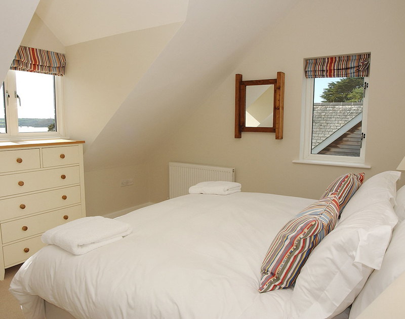 A comfortable bedroom with far reaching Camel Estuary views from the window at Medrose 2, a self catering holiday house to rent in Rock, North Cornwall.