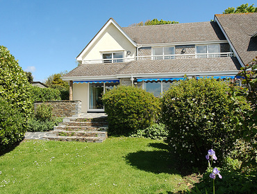 The rear exterior and south-facing garden of September Corner, a popular holiday rental in Rock, Cornwall, with elevated patio.