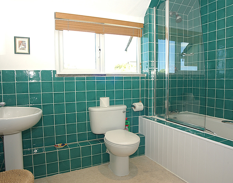 Smart aquamarine tiles decorate this bathroom at September Corner, a holiday house in Rock, Cornwall
