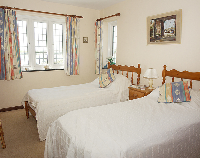 The twin bedroom of Cocklebar, holiday cottage to rent in Rock, Cornwall, with its lovely estuary views.