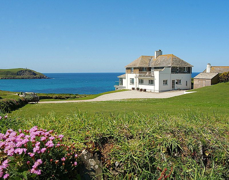 The exterior view of Spindrift, a luxury holiday house near Daymer Bay, Cornwall, with its large grounds and seaside setting.
