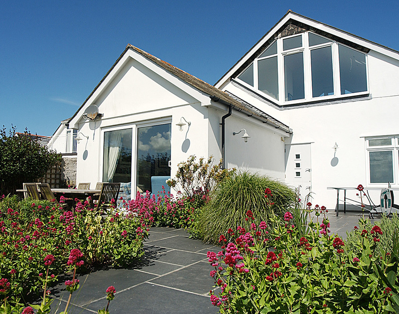 The exterior view of The Point, a splendid holiday house to rent in Polzeath, Cornwall, with well-planted garden.