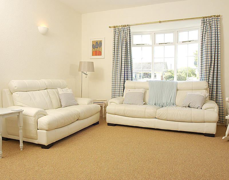 The sitting room with two comfortable sofas in Musters, a holiday rental in Rock, North Cornwall.