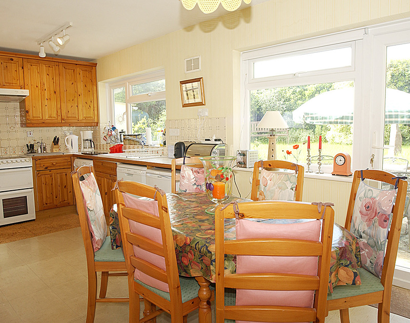 The colourful kitchen and dining room at Little Sands, a self catering holiday rental in Rock, Cornwall.