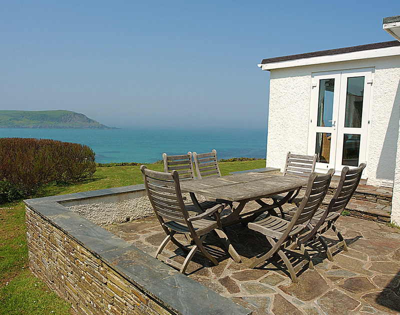 The breathtaking sea view from the terrace at Thalassa, with teak patio furniture above Daymer Bay on the North Cornish Coast.