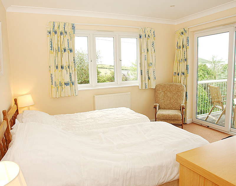 One of two twin bedrooms at Thyme Bank, a holiday house to rent at Daymer Bay, Cornwall, with doors to the garden.