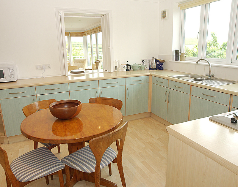 Attractive, modern kitchen of Thyme Bank, a holiday house at Daymer Bay, Cornwall, with small breakfast table.