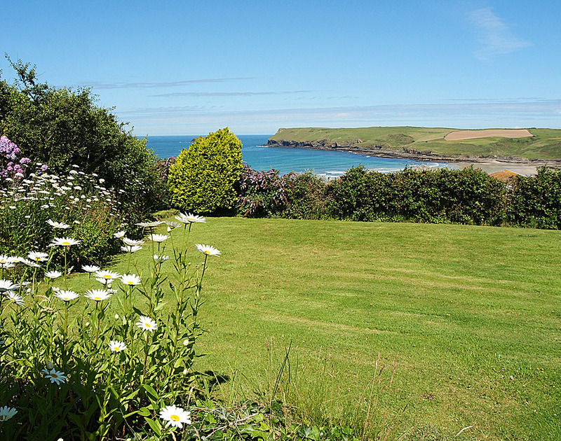 The pretty bordered garden and magnificent sea views towards Pentire Point from Trewint, a self catering holiday rental on the coast at Polzeath, North Cornwall.