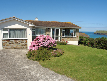 The exterior view of Trewint and the stunning sea views towards Pentire Point in this self catering holiday bungalow in Polzeath, Cornwall.