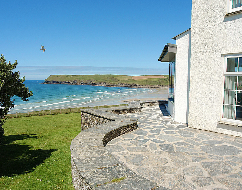 The garden and sea views towards Pentire Point from the terrace at Treviles, a cllif top self catering holiday house in Polzeath, North Cornwall.