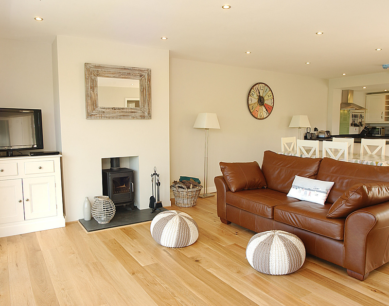 Attractive and bright sitting room of Pebblestones, a holiday cottage in Port Isaac, Cornwall, with its woodburner.
