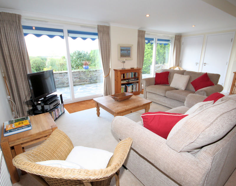 The well-furnished sitting room of September Corner, holiday house in Rock, Cornwall, with doors to the patio.