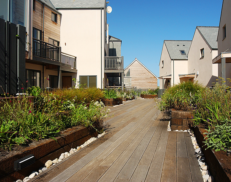 The well designed outside space with decking and attractive flower beds at The Beach Hut, a dog friendly, self catering holiday house in Polzeath, Cornwall.