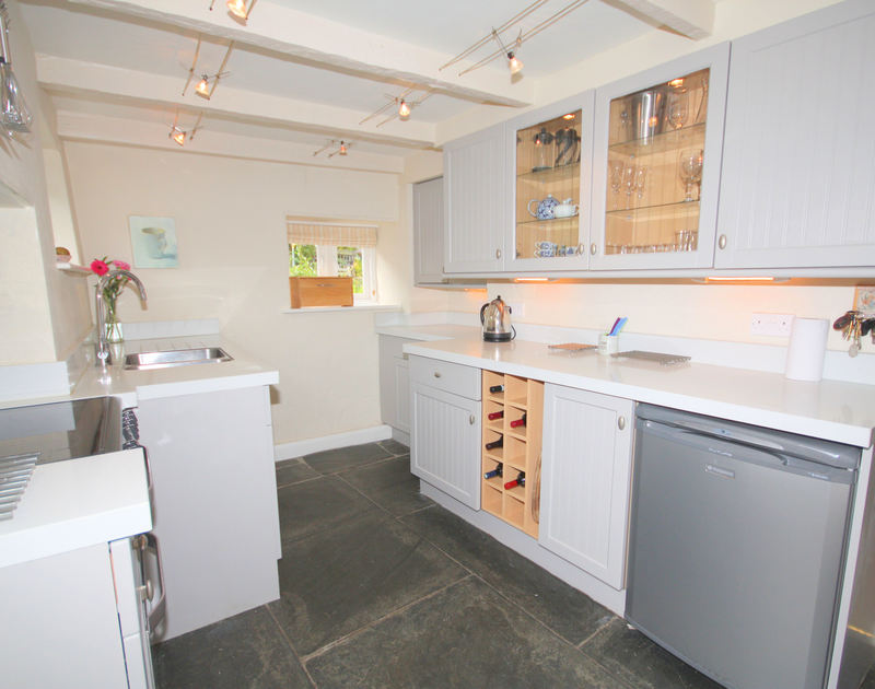 Stylish fitted kitchen of Brook Cottage, a holiday house in Port Isaac, Cornwall, with ample work surfaces.