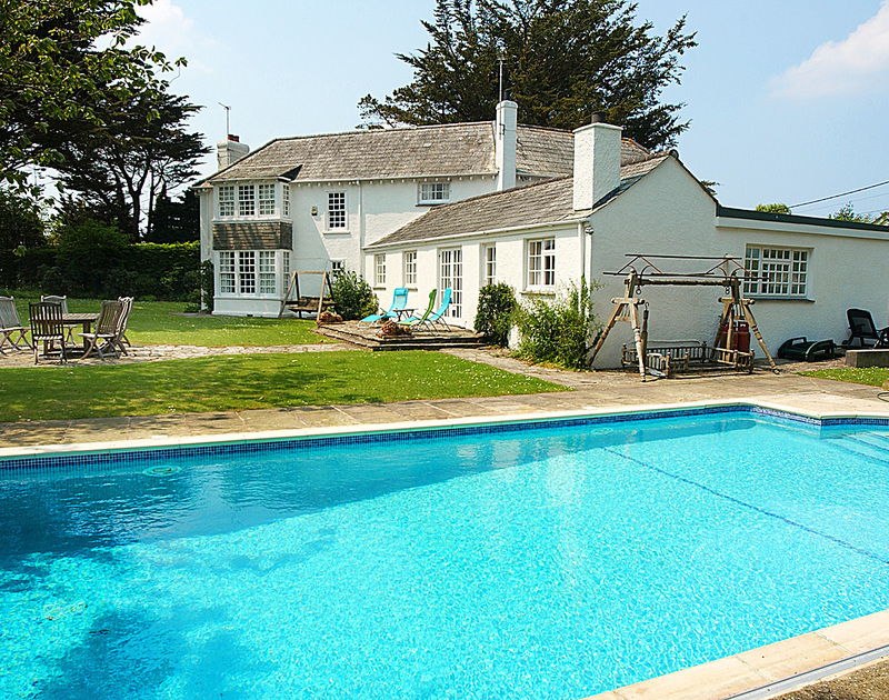The heated swimming pool and garden of Trewiston Cottage, a holiday house at Daymer Bay, Cornwall