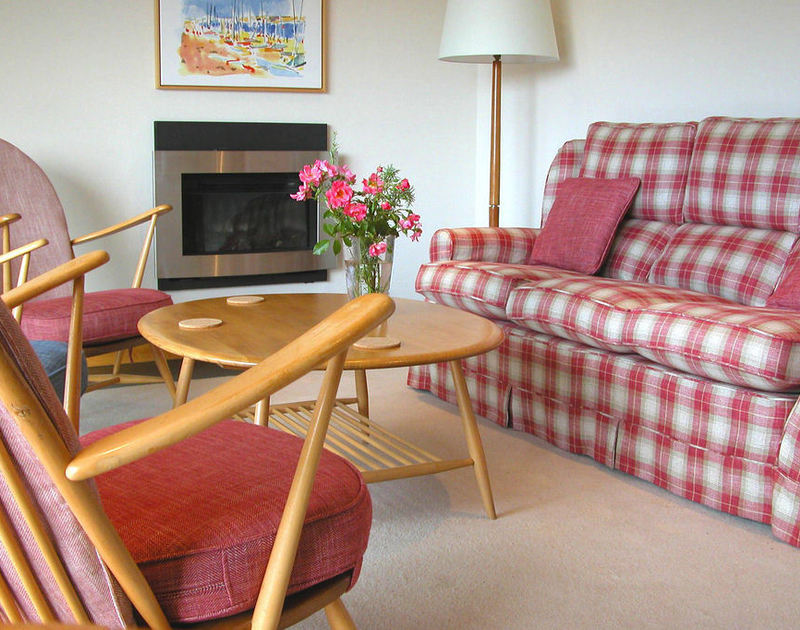 The sitting room of Rosevallen, a charming holiday cottage to rent at Daymer Bay, Cornwall, with its colourful soft furnishings.