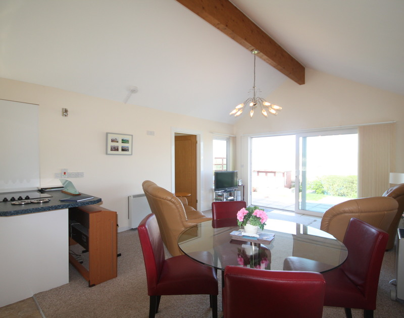 The open plan living areas and the glass sliding doors to the garden with far reaching sea views at Dozmary, a self catering holiday rental in Polzeath, Cornwall.