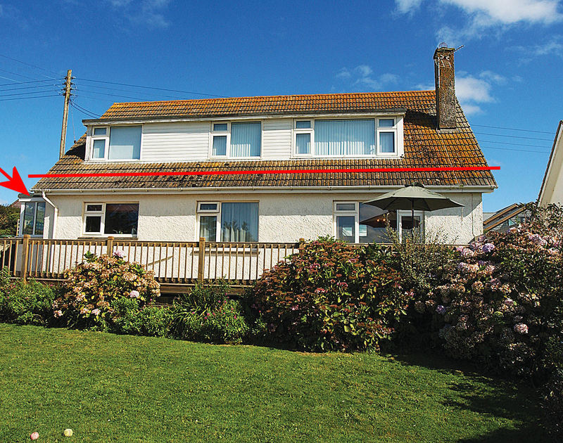 An exterior view of Bella Vista, a ground floor apartment in Polzeath, Cornwall, with its sunny balcony and lawned garden.
