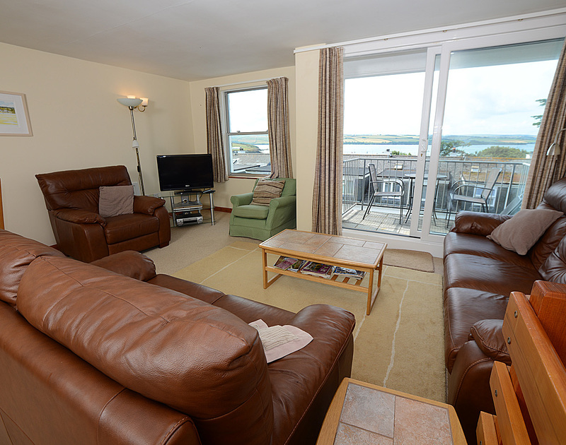 Well-furnished sitting room and balcony at Slipway 14, a holiday rental in Rock, Cornwall, with lovely Camel Estuary views.