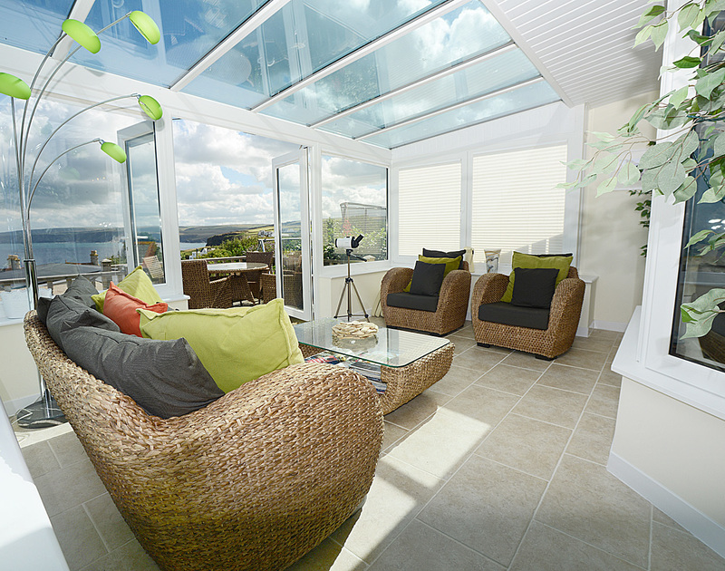 The sunny conservatory at Merlin's View in Port Isaac, Cornwall, with far reaching sea and coastal views.