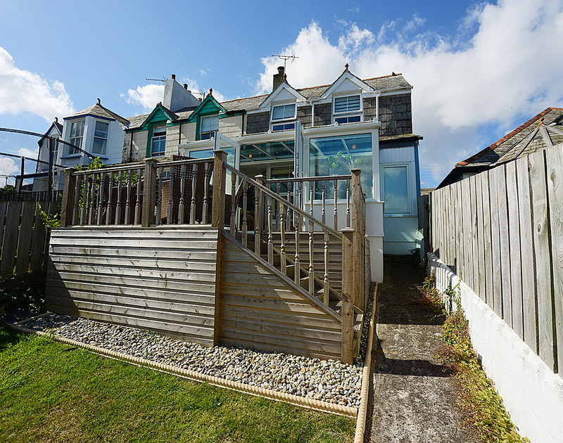 The decked exterior of Merlin's View, a holiday house in Port Isaac, with steps down to the garden.