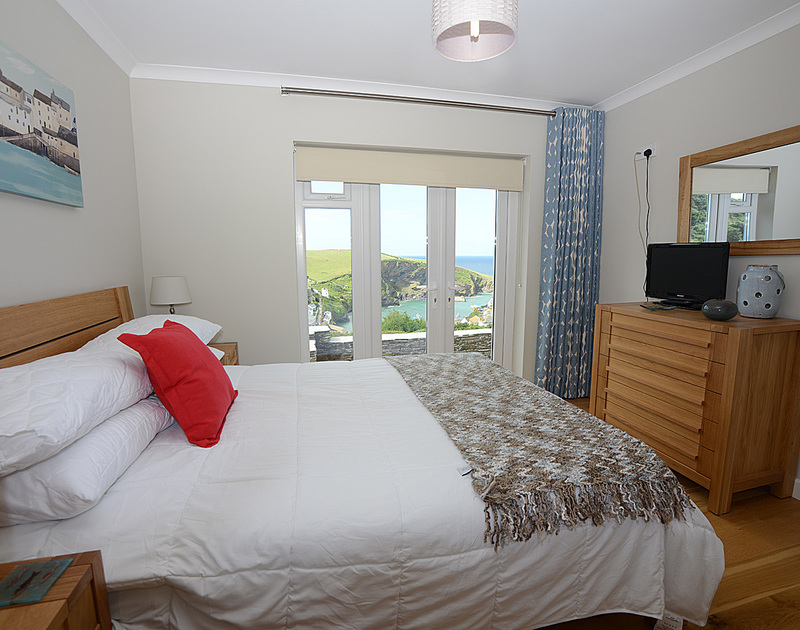 En suite double bedroom with sea views at Pebblestones, a holiday cottage in Port Isaac, Cornwall, with TV and doors to the patio.