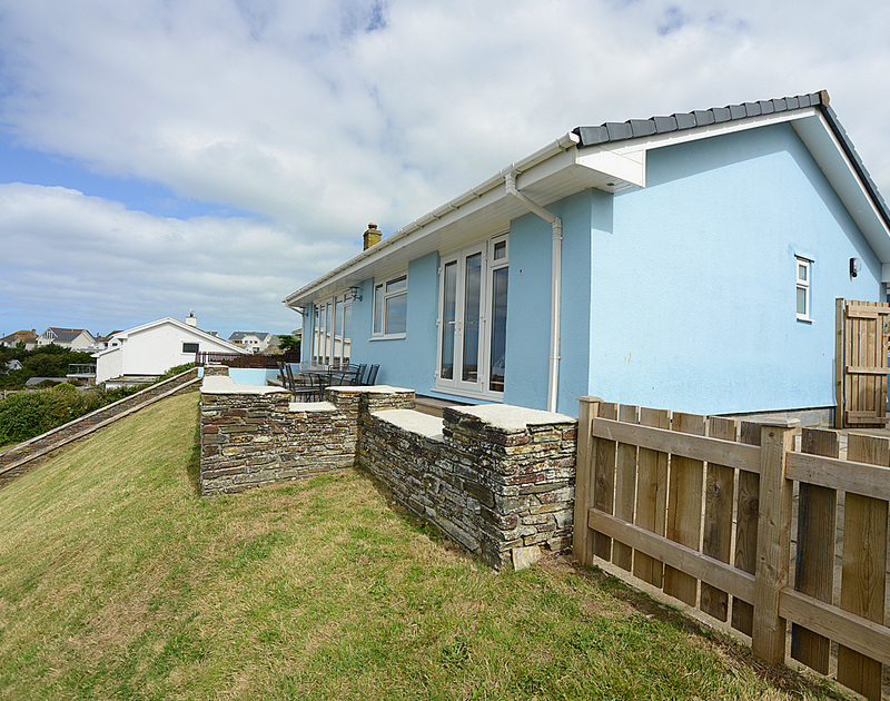 Exterior view of Pebblestones, a holiday cottage in Port Isaac, Cornwall, with lawned sloping front garden.