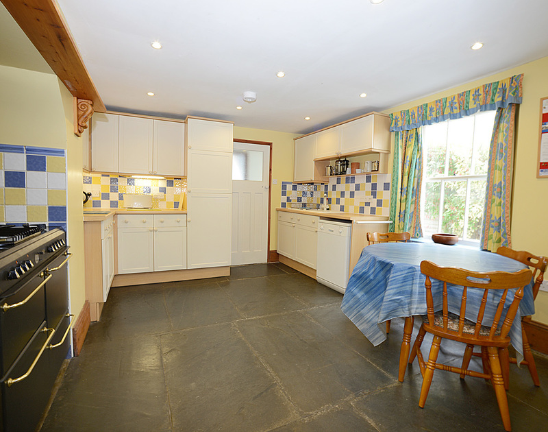 The spacious kitchen with fabulous slate flooring in Seaward, a three storey, Edwardian, family holiday house to rent above the beach at Port Gaverne in Port Isaac in Cornwall.