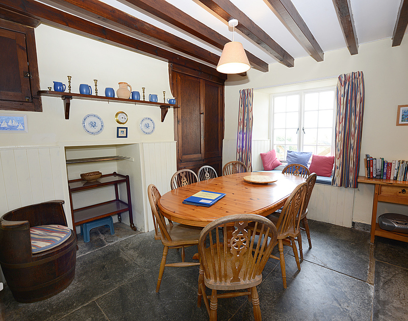 The attractive and characterful dining room of Ivy Cottage, a holiday house in Polzeath, Cornwall, with its flagstone floor.
