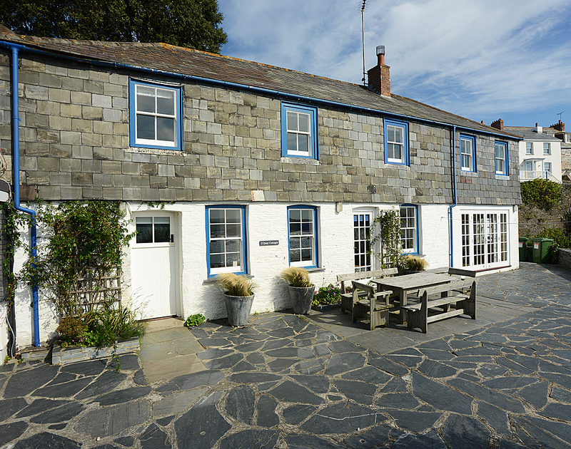 A view of the front of 2 Quay Cottage, a well located holiday rental in Rock, Cornwall, with its large paved patio and seating area.