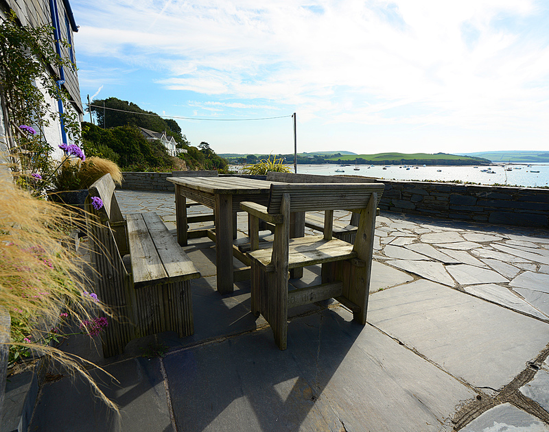 The spacious, slate patio of 2 Quay Cottage, holiday cottage in Rock, Cornwall with its panoramic view of the Camel Estuary.