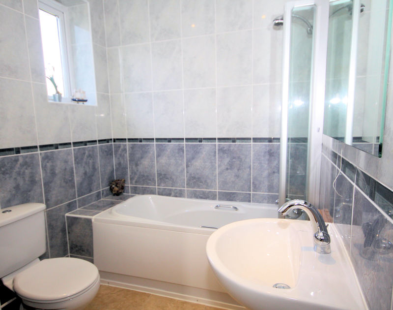 The fully tiled, modern bathroom at Higher Crawallis, a holiday rental near Daymer, Cornwall