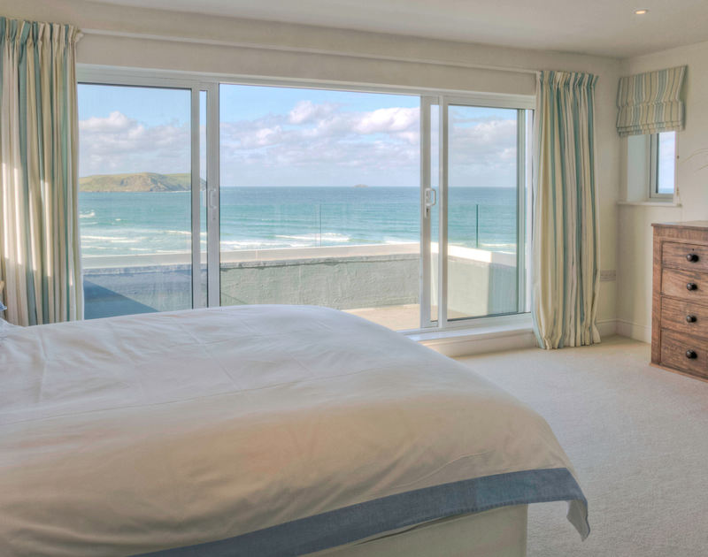 The impressive master bedroom with sliding glass doors and a balcony with unforgettable sea views at Treverden, a holiday house to rent in New Polzeath, Cornwall.