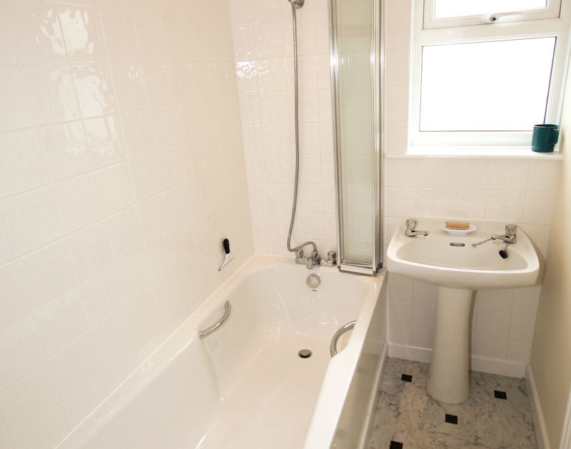 Glossy white tiles in the bathroom of Zapadiah, a self-catering holiday let in Polzeath, Cornwall