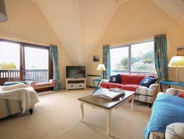 The spacious lounge showing patio doors out to the balcony with rural views form Hatchlands, a self catering holiday house to rent in Rock, North Cornwall.