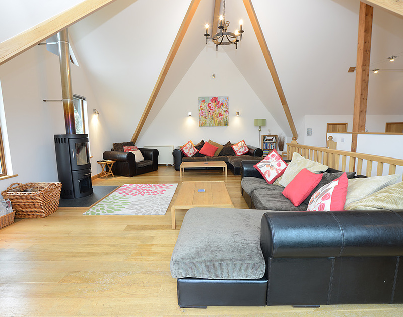 The large sitting room of 8 Sandy Hills, holiday accommodatoin in Rock, with lots of comfy sofas and a woodburner.